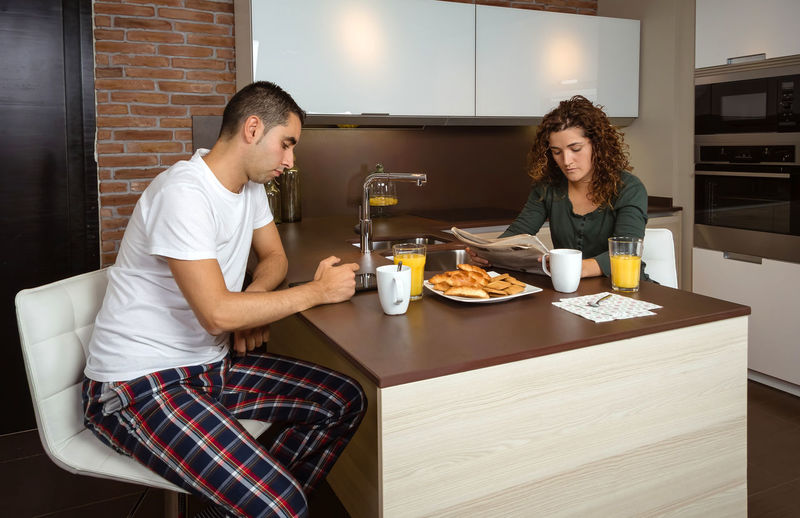 Young couple having breakfast in the kitchen bored of the daily routine Horizontal Pajama Croissant Cookies Orange Juice  Girlfriend Relaxing Husband Boyfriend Wife Relationship Lifestyle Love Cup Caucasian Healthy Two Coffee Glass Girl Meal Drink Together Young Woman Kitchen Man Indoors  Food Technology Newspaper Digital Tablet News Read Bored Serious Male Home People Female Breakfast Morning Couple Problems Boredom Daily Routine Monotony
