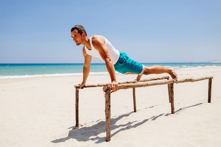 Man training and workout on beach. Fitness outdoors. Beach One Person Sand Sea Ocean Fitness Fitness Training Outdoors Man Males  Strong Yoga Stretching Workout Sport Leisure Activity Lifestyles Relaxing Exercising Sunlight Push Ups
