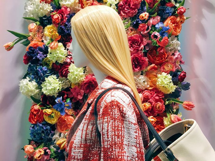 Close-up of mannequin against flowers
