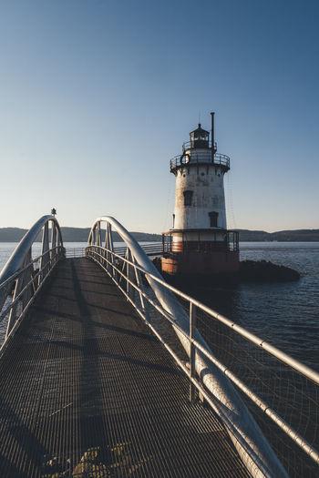 Bridge over sea by lighthouse against clear sky