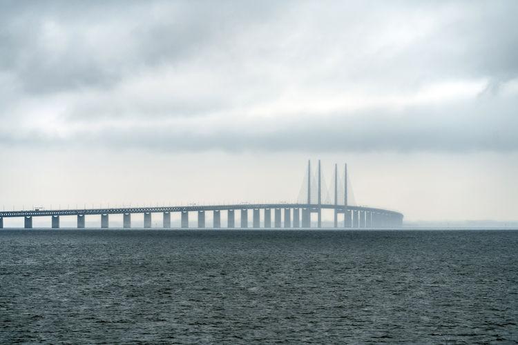 Suspension bridge over sea against cloudy sky