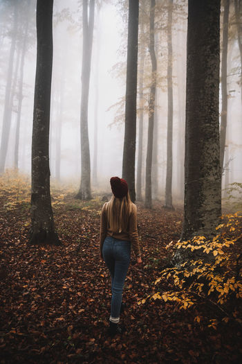Full length of woman standing by tree in forest during autumn