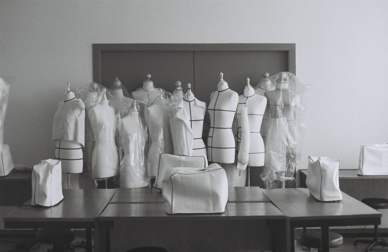 Mannequins and table against wall in room