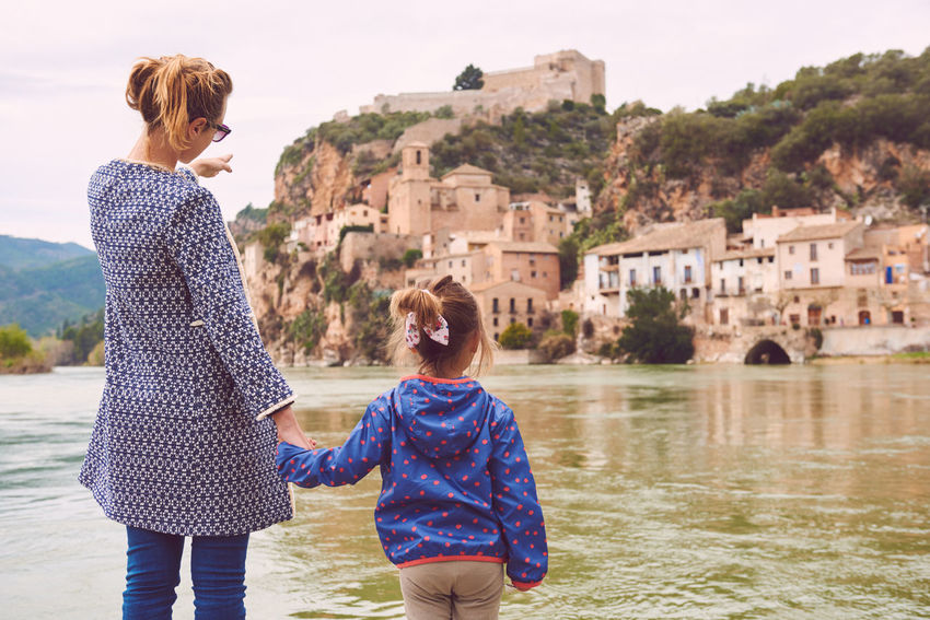 Mother and daughter travellers enjoying view of the Miravet village and Ebro river. Province of Tarragona. Spain Ancient Architecture Castle Catalonia Coast Daughter Ebro River Europe Family Famous Place Fortification History Landmark Landscape Miravet Mother People Picturesque Village Riverside SPAIN Tarragona Travel Destinations Typical Spanish Village Waterside Woman