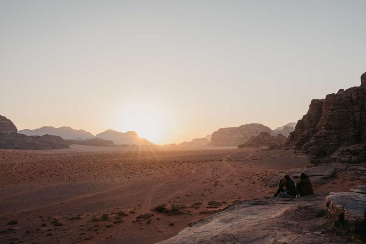 Women sitting on desert against sky during sunset