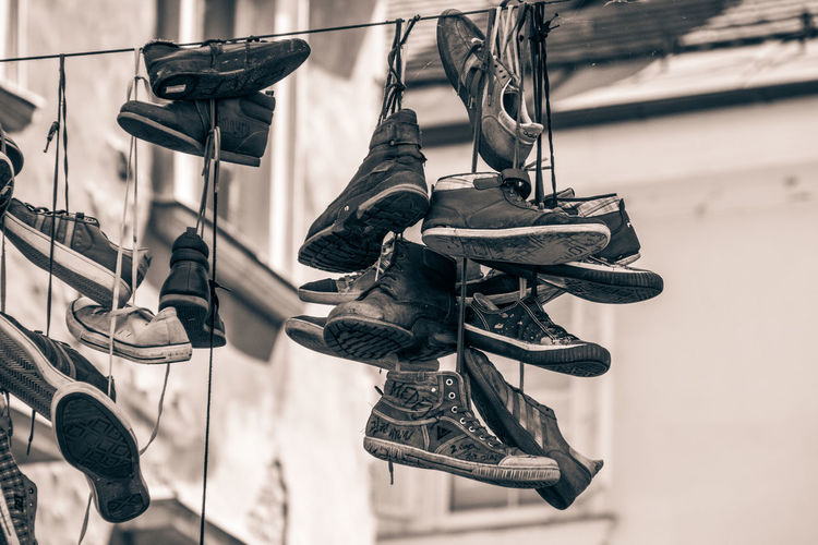 Low angle view of shoes hanging on metal
