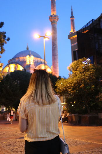 Rear view of woman with blond hair standing in city at dusk