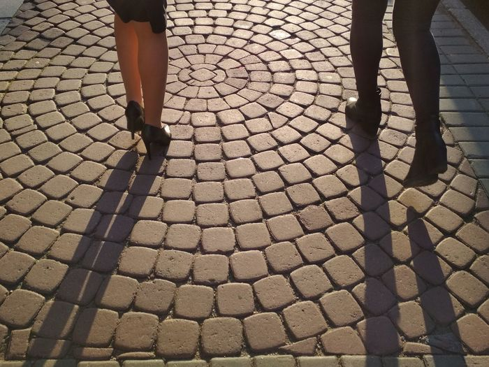 Low section of friends walking on cobbled street