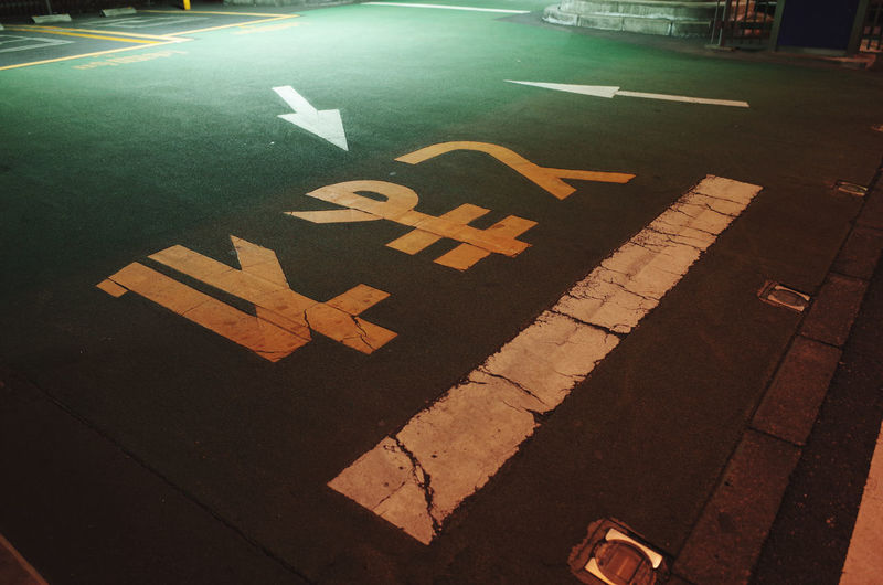 High angle view of arrow sign on street at night