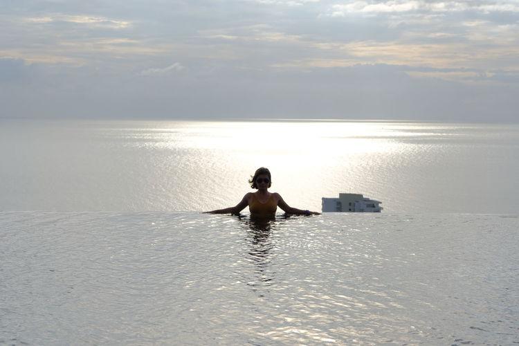 Woman relaxing in infinity pool against sea