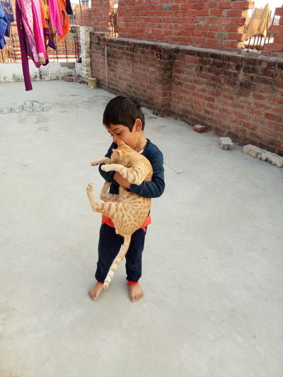 Full length of boy holding cat while standing at terrace