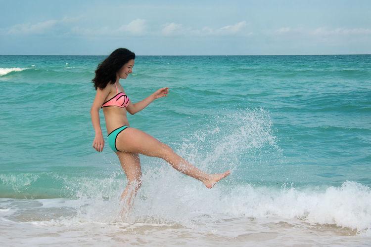 Side view of woman splashing water in sea