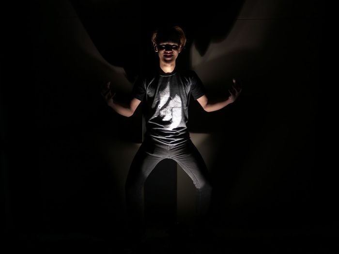Portrait Of Young Man Standing In Illuminated Dark Room