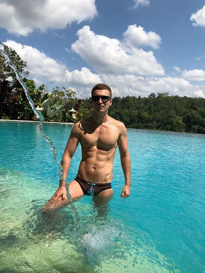 Portrait of shirtless muscular man standing in sea during summer