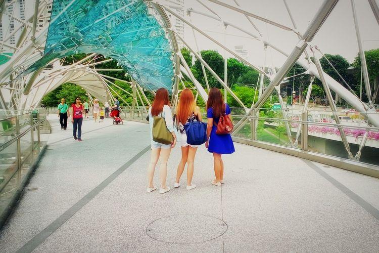 Rear view of women standing at helix bridge