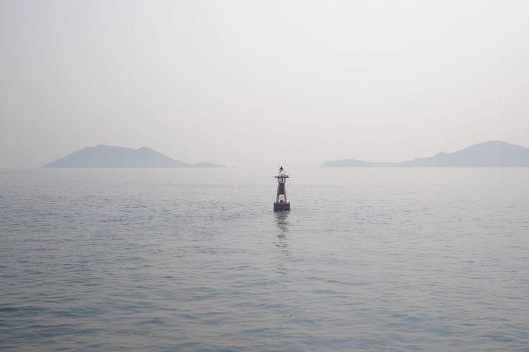 Buoy amidst sea against clear sky