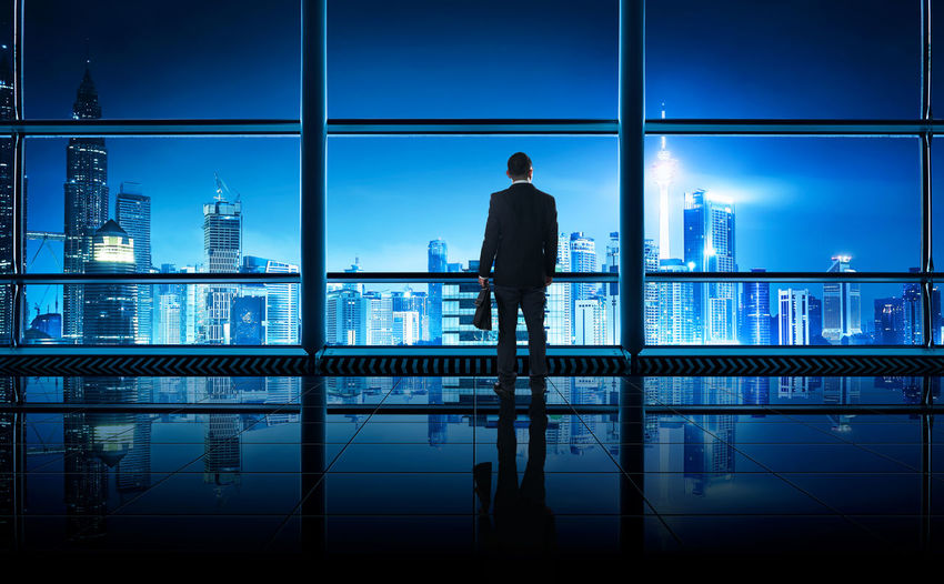 Businessman looking at cityscape through glass window in office building