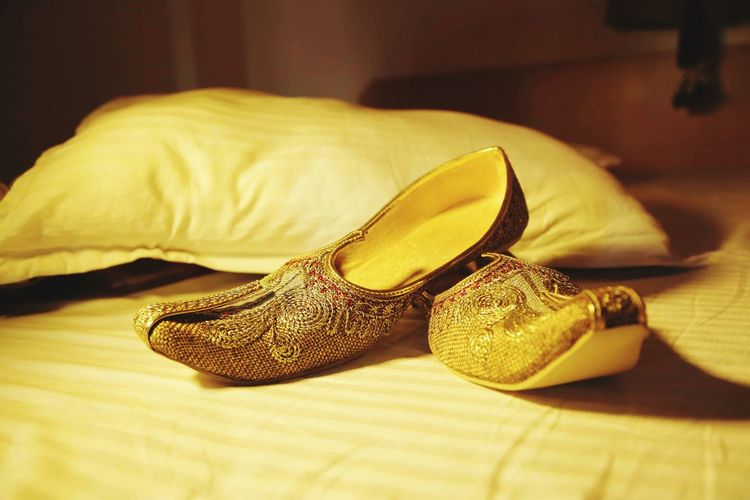 Close-up of traditional shoes by cushion on bed