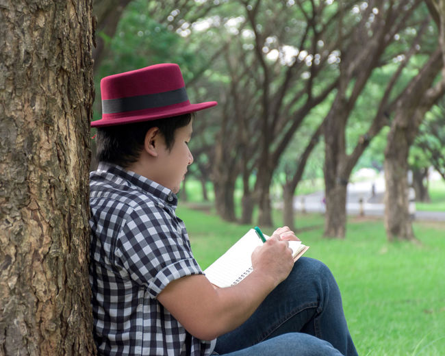 Natural Tree Plant One Person Real People Tree Trunk Casual Clothing Child Leisure Activity Three Quarter Length Focus On Foreground Holding Sitting Day Childhood Side View Clothing Lifestyles Outdoors Pre-adolescent Child Sketchbook Sketch Under Tree Write