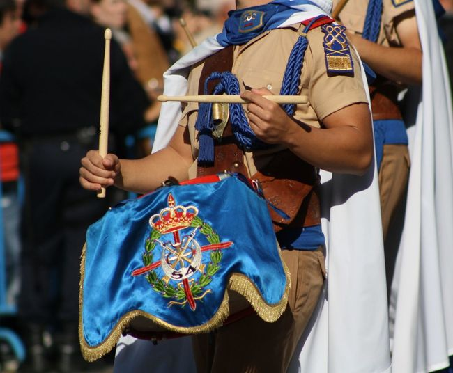 Midsection of woman playing drum while marching