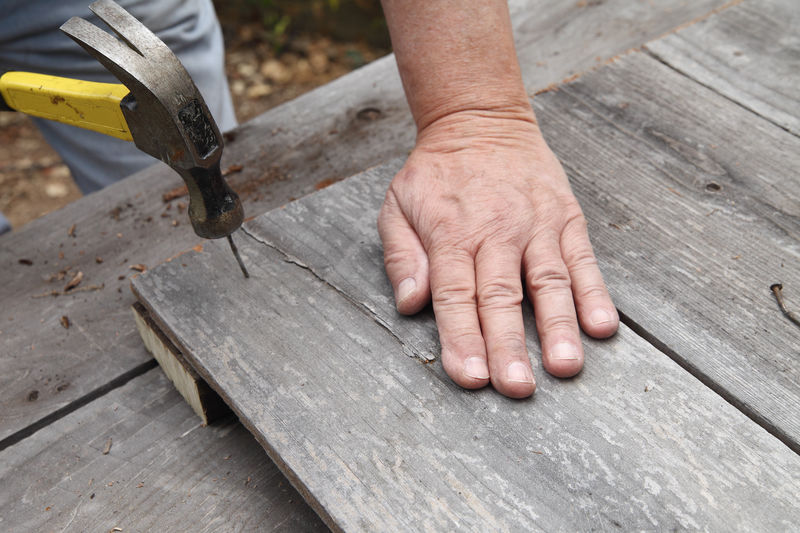 Cropped image of hand hammering nail on wooden plank