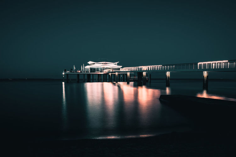 Illuminated pier by sea against clear sky at night