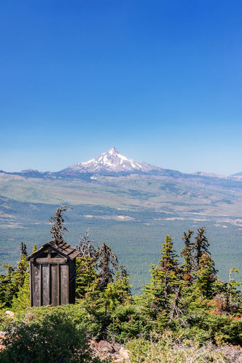 Vertical view of an outhouse and Mt. Jefferson as seen from Black Butte in Central Oregon Oregon Bend Mt Jefferson Mount Jefferson Jefferson Mountain Cascades Cascade Mountains Volcano Landscape Northwest Pacific Northwest  Summer Forest Pine Tree Pine Trees Mountain Peak Mountain Range USA No People Nature Beauty In Nature Sky Outhouse Bathroom