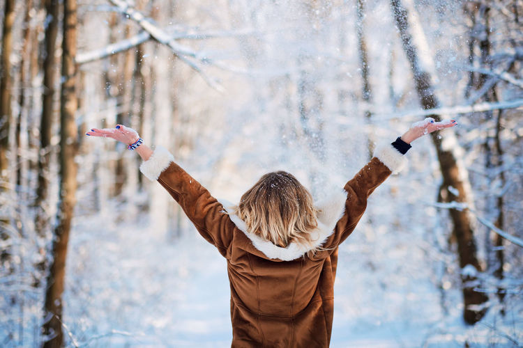 Adult Arms Outstretched Arms Raised Clothing Cold Temperature Day Focus On Foreground Hair Hairstyle Human Arm Human Limb Leisure Activity Lifestyles Limb One Person Outdoors Real People Rear View Snow Standing Tree Warm Clothing Winter