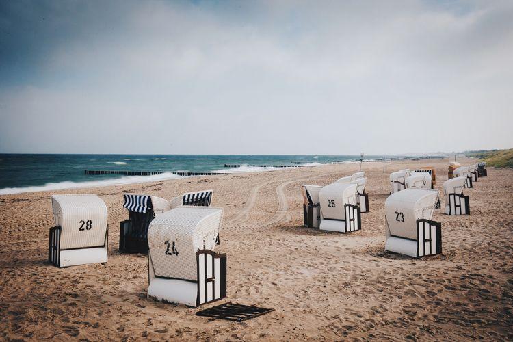 Hooded Beach Chair On Beach Against Cloudy Sky