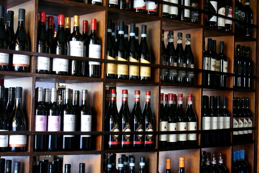 A nice variety of wine bottles on wooden shelves. Abundance Arrangement Backgrounds Bottles Collection Display Enoteca Full Frame In A Row Large Group Of Objects Libation Light And Shadow Multi Colored No People Shelf Side By Side Still Life Variation Vino Wine Beautifully Organized Wine Moments