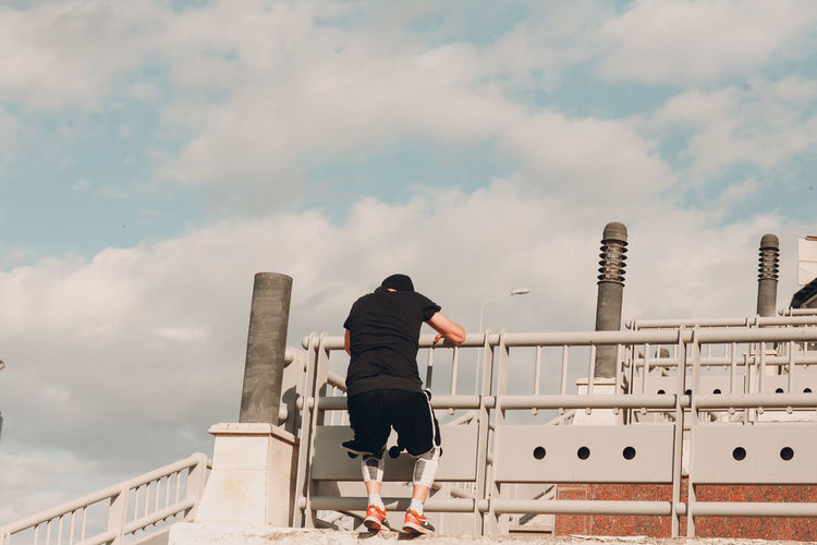 Rear view of man standing by railing against sky