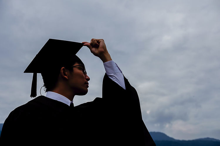 Low Angle View Of Man In Graduation Gown And Mortarboard Against Sky