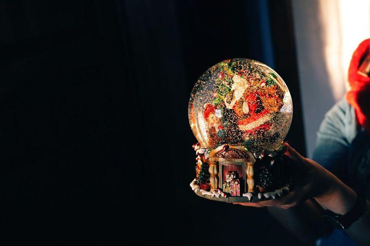 Cropped hand holding christmas decoration globe