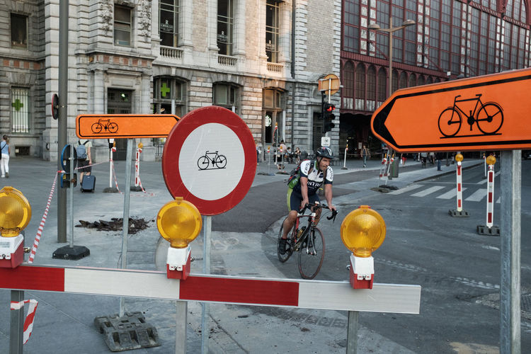 Cyclist between signs Architecture Building Exterior Built Structure Car City City Life City Street Communication Crosswalk Day Guidance Information Light No People Outdoors Road Road Sign Sign Street Symbol Text Transportation Western Script