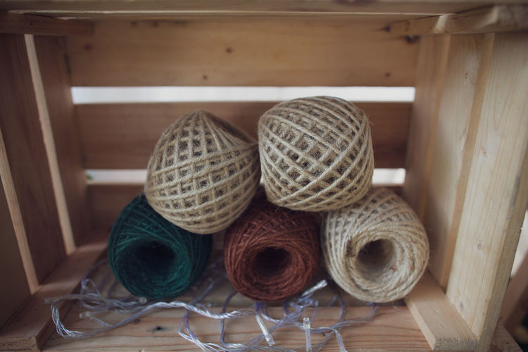 Close-up of thread spools in wooden container