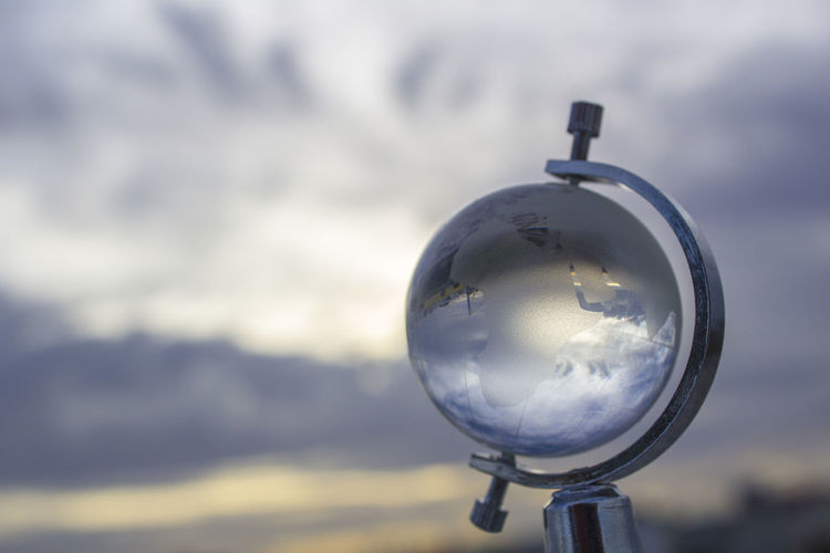 Close-up of glass globe against cloudy sky