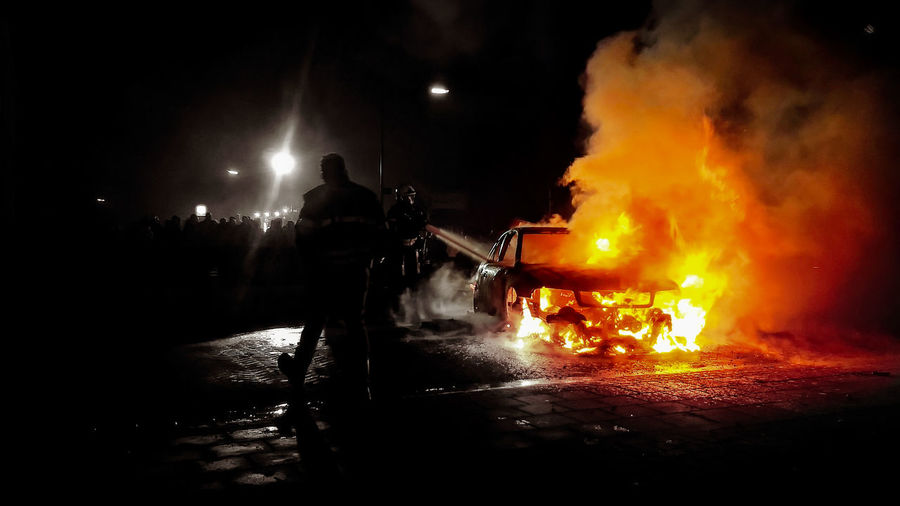 Firefighters standing by burning car on street at night