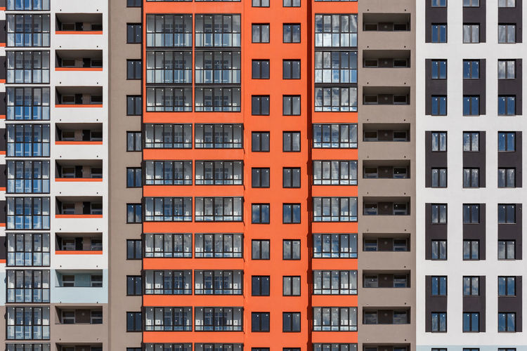 Full frame background of new high rise apartament building wall with multiple balcony and windows