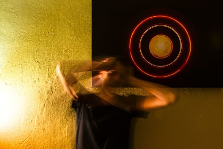 Digital composite image of person holding illuminated light against wall
