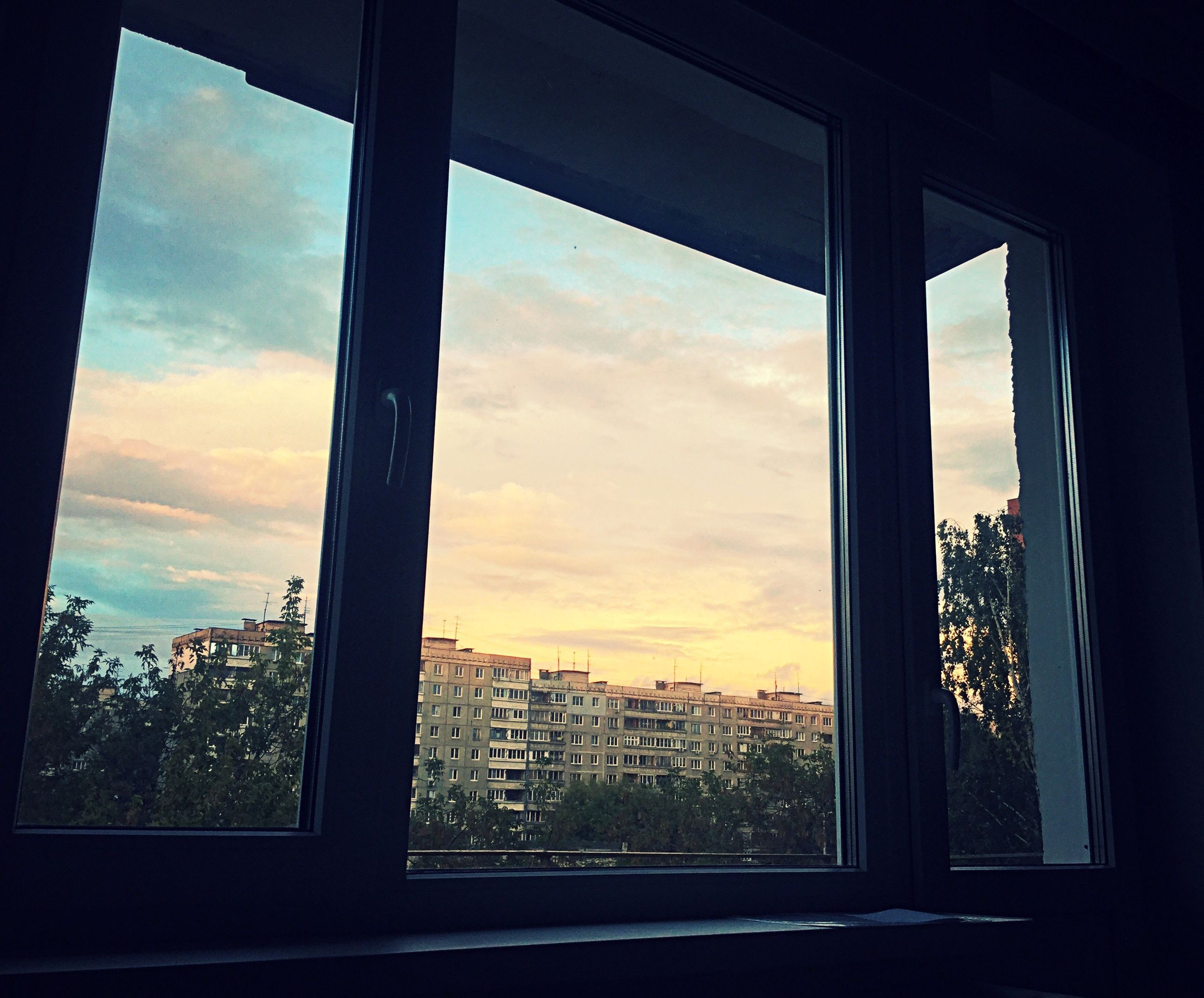 window, indoors, architecture, built structure, home interior, city, sunset, cityscape, transparent, glass - material, sky, building exterior, urban skyline, geometric shape, cloud - sky, no people, window frame, darkness, architectural column, development, tall