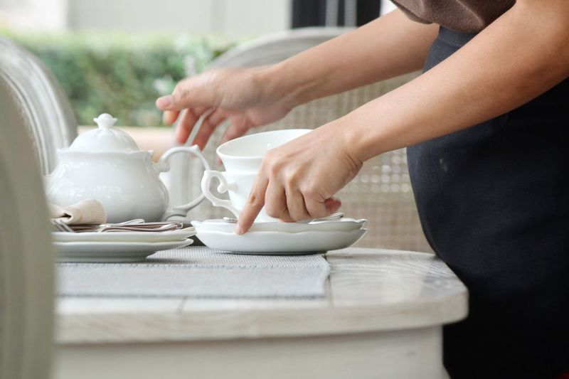 Midsection Of Woman Picking Crockery From Table