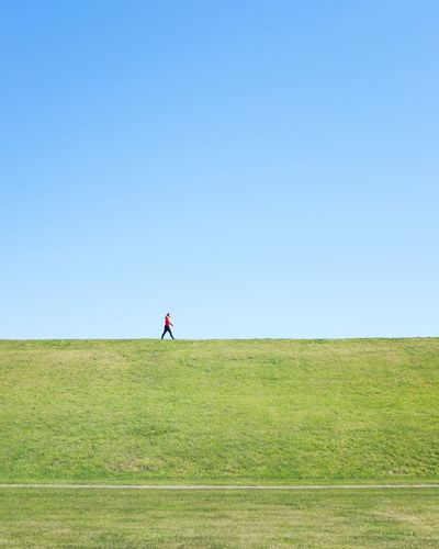 Woman standing on field against clear sky