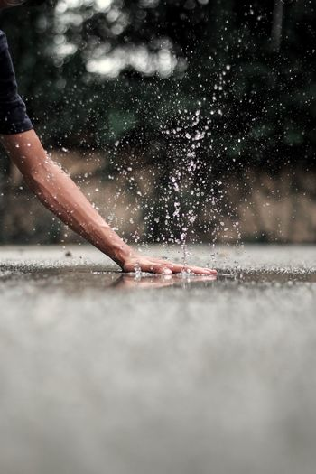 Cropped hand splashing water on road