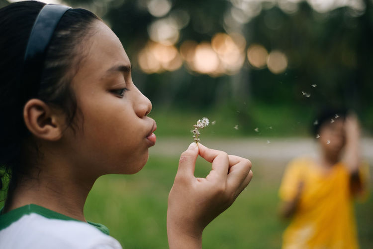 Close-up of girl blowing flower