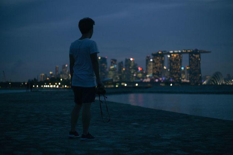 Full Length Rear View Of Man Standing By Illuminated Marina Bay Sands At Dusk