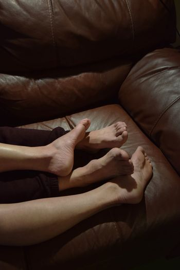 Low section of couple sleeping on sofa at home