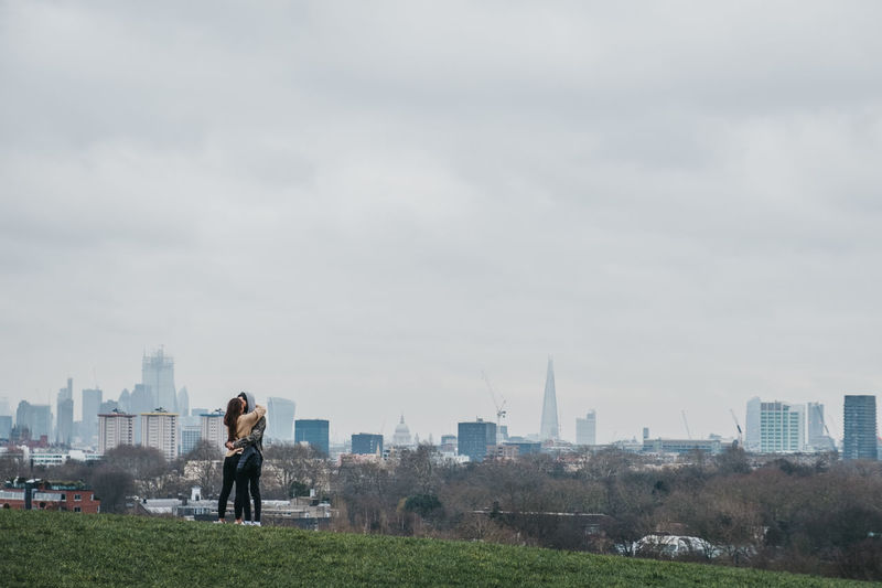 Couple hugging on top of Primrose Hill, city skyline on the background, London, UK. People Tourism Travel Park Everyday Life Youth Culture Copy Space Sky Standing Outdoors Positive Emotion Skyline Traveling Young Adult Concept Love Real People Cityscape City Couple - Relationship Primrose Hill Uk London Lifestyles Modern