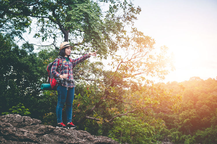Woman pointing while standing against trees