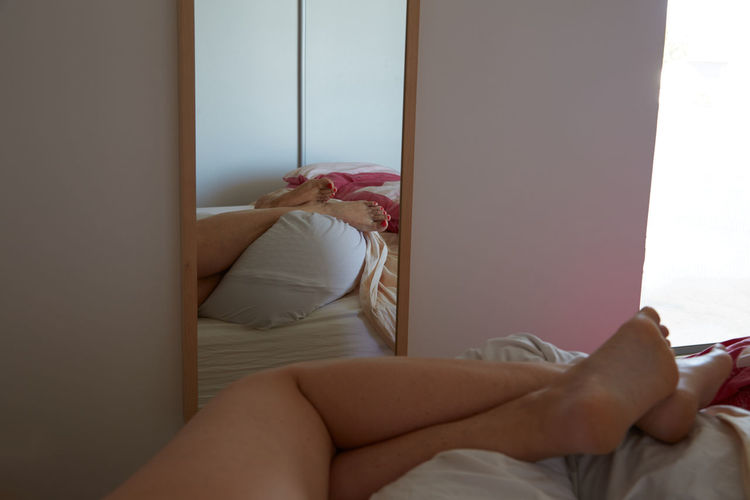 Low Section Of Seductive Woman Sleeping On Bed By Mirror On Wall
