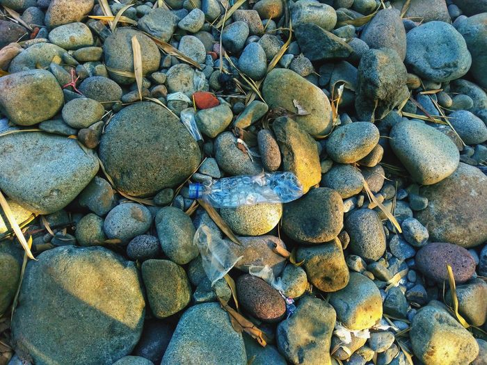 plastic bottle on pile of mountain rocks Plastic Bottle Pile Of Stones Plastic Pile Of Rocks Rock Stone Pebble Beach Beach Backgrounds Full Frame Pebble Textured  Pattern Close-up Rugged Boulder Coast Stone - Object Rock Formation Natural Arch